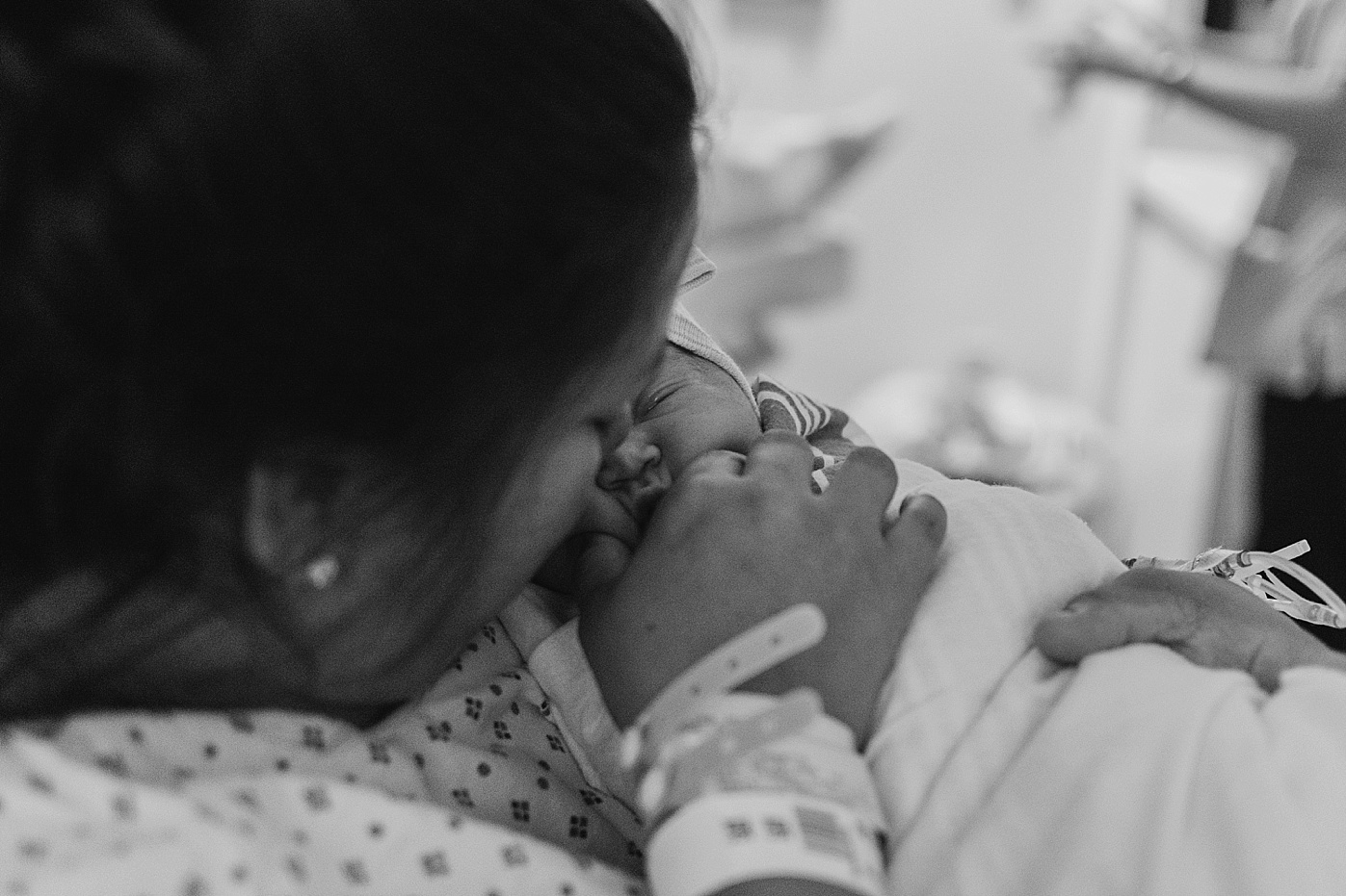 mom holding newborn baby girl squeezing cheeks documentary candid family photography