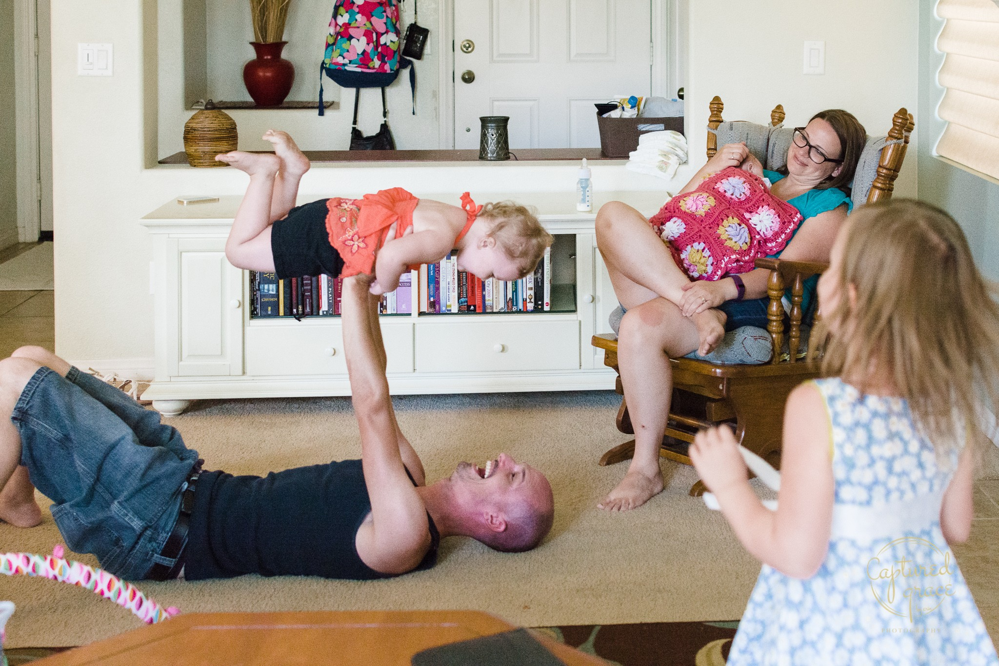dad playing with daughters mom nursing infant documentary candid family photography
