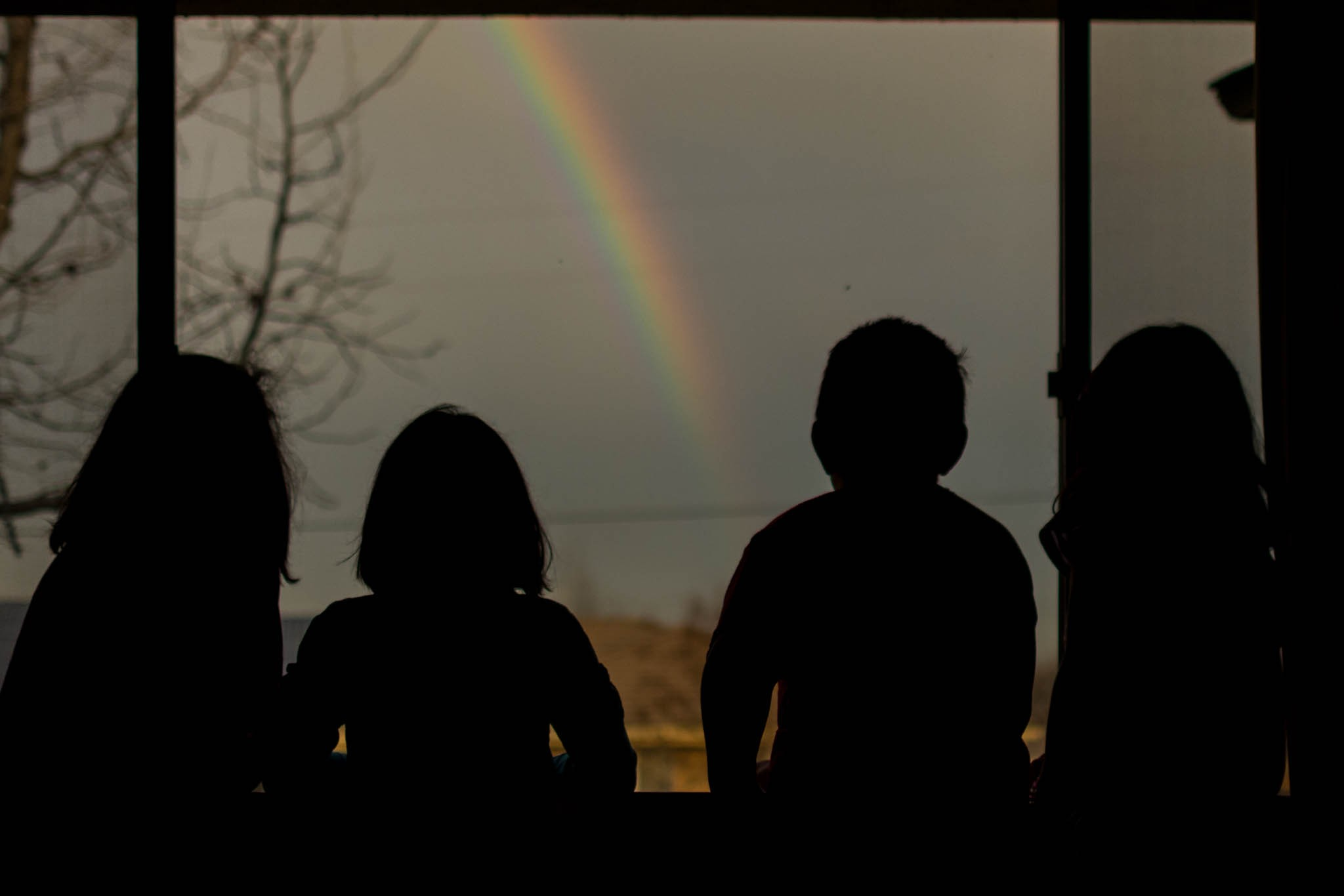 silhouette of kids looking at rainbow documentary candid family photography