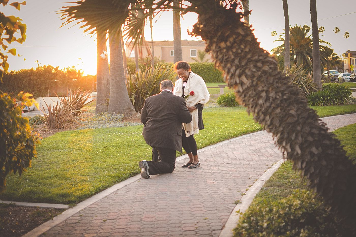 woman holding rose smiling as man proposes, seal beach, sunset, captured grace by erin