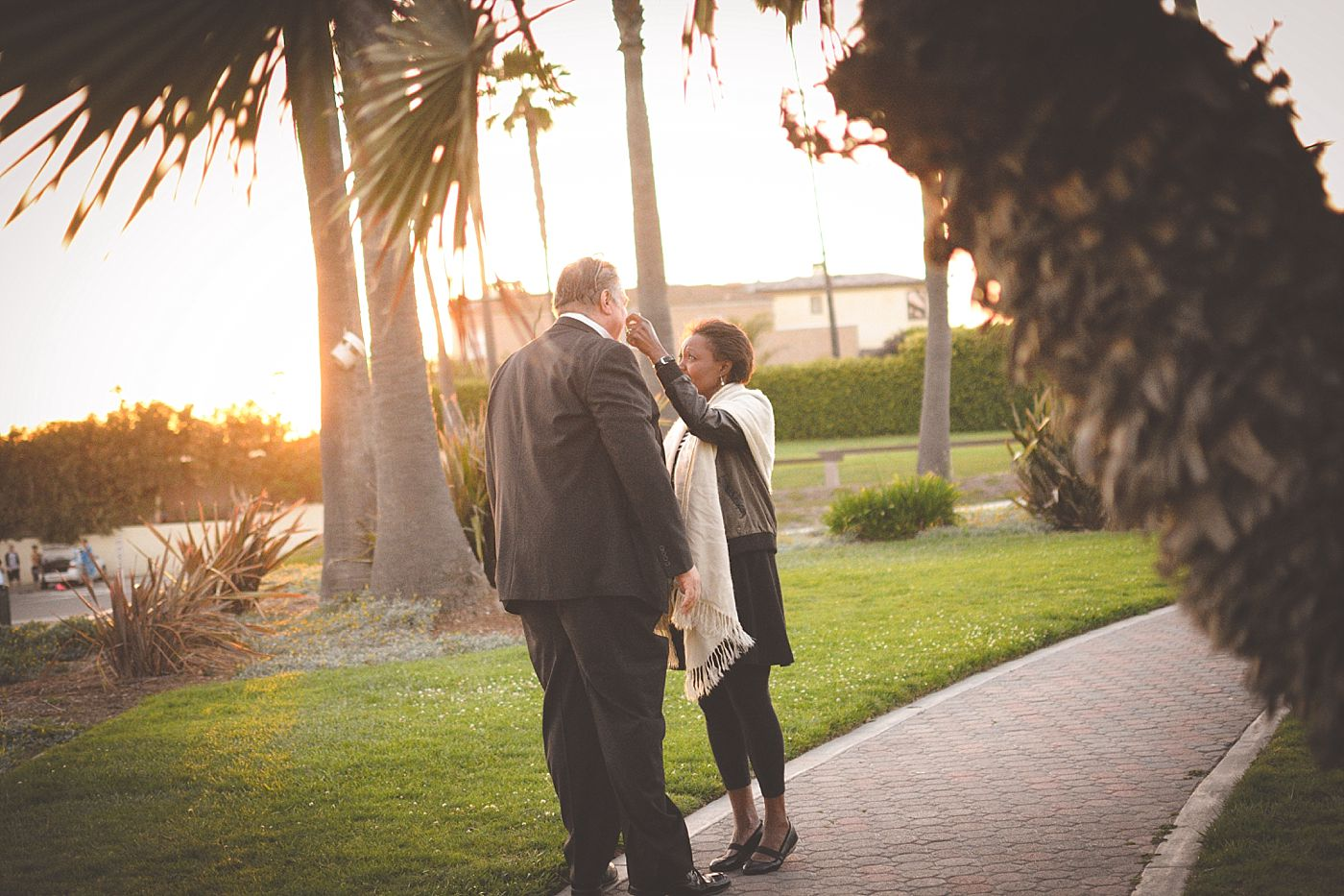 woman wipes tear off mans face after sunset proposal seal beach captured grace by erin