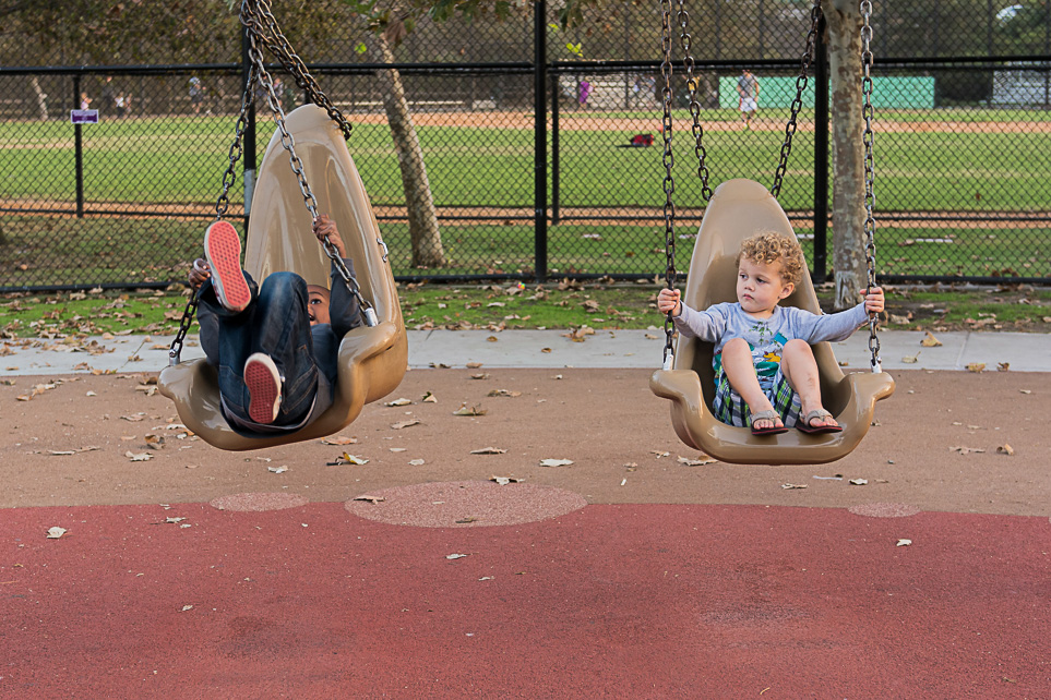 Toddlers on swings on playground family photography