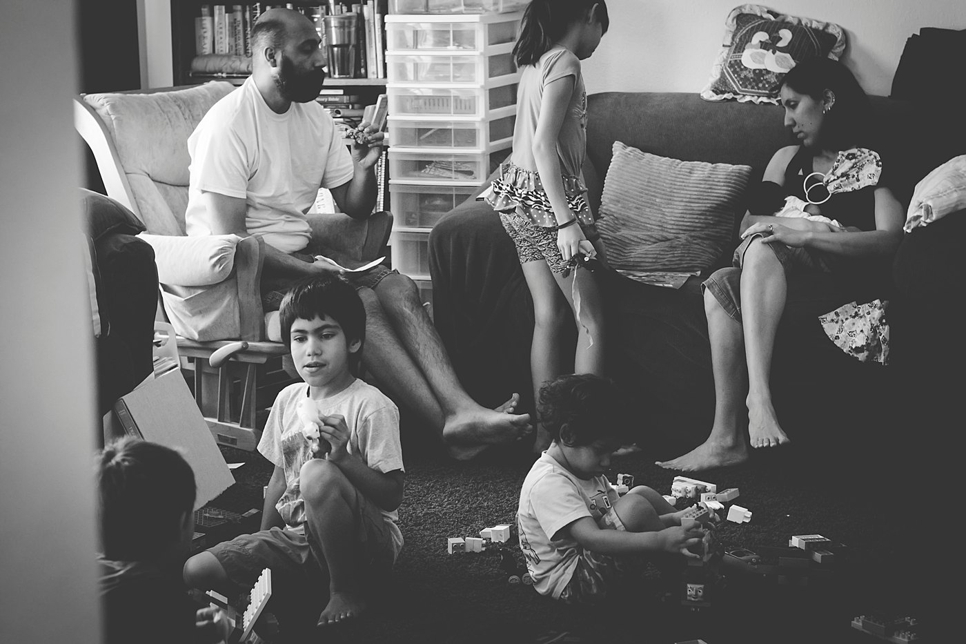 mom breastfeeding baby surrounded by older kids and husband captured grace by erin family photographer