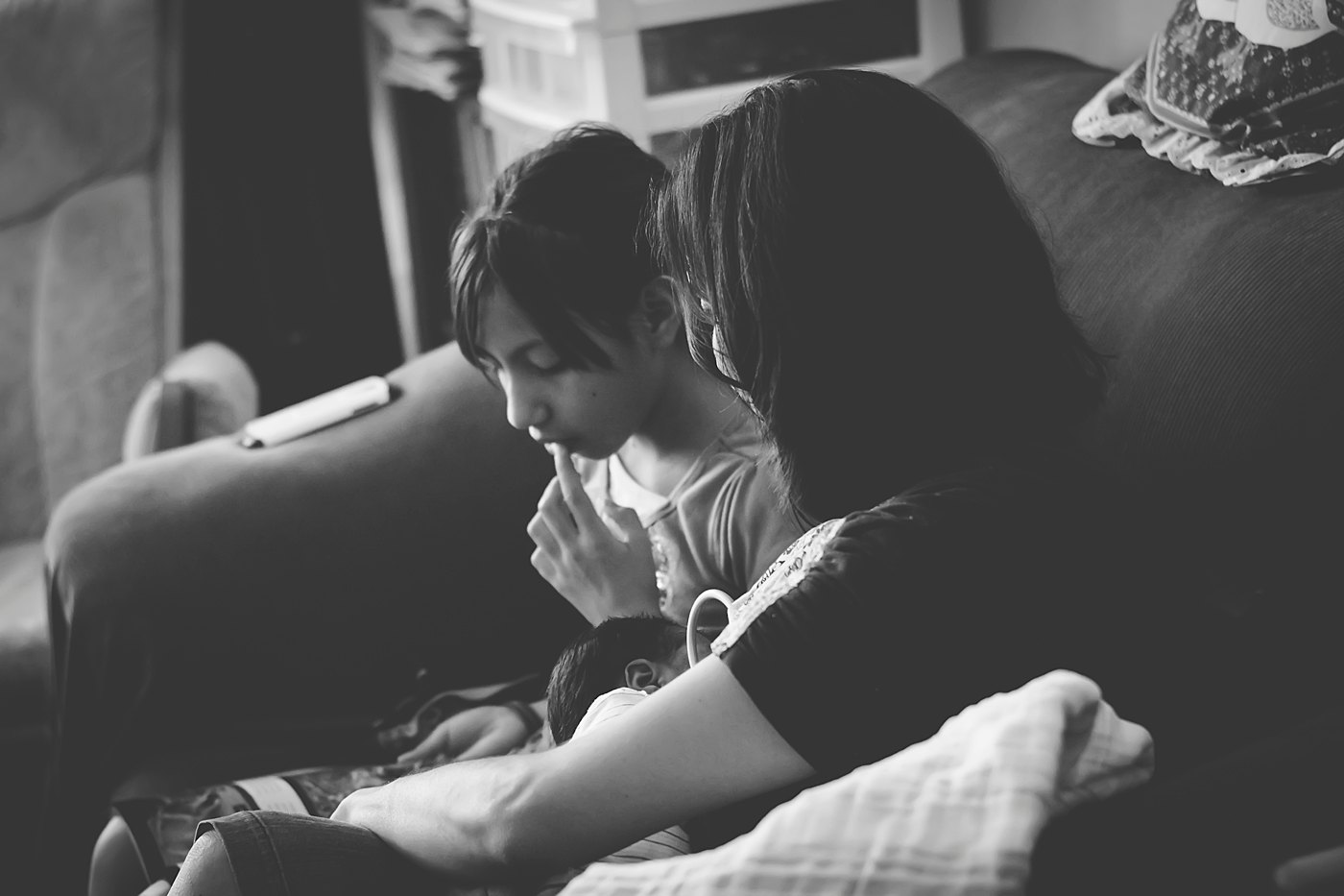 mom nursing while talking to older daughter captured grace by erin family photography