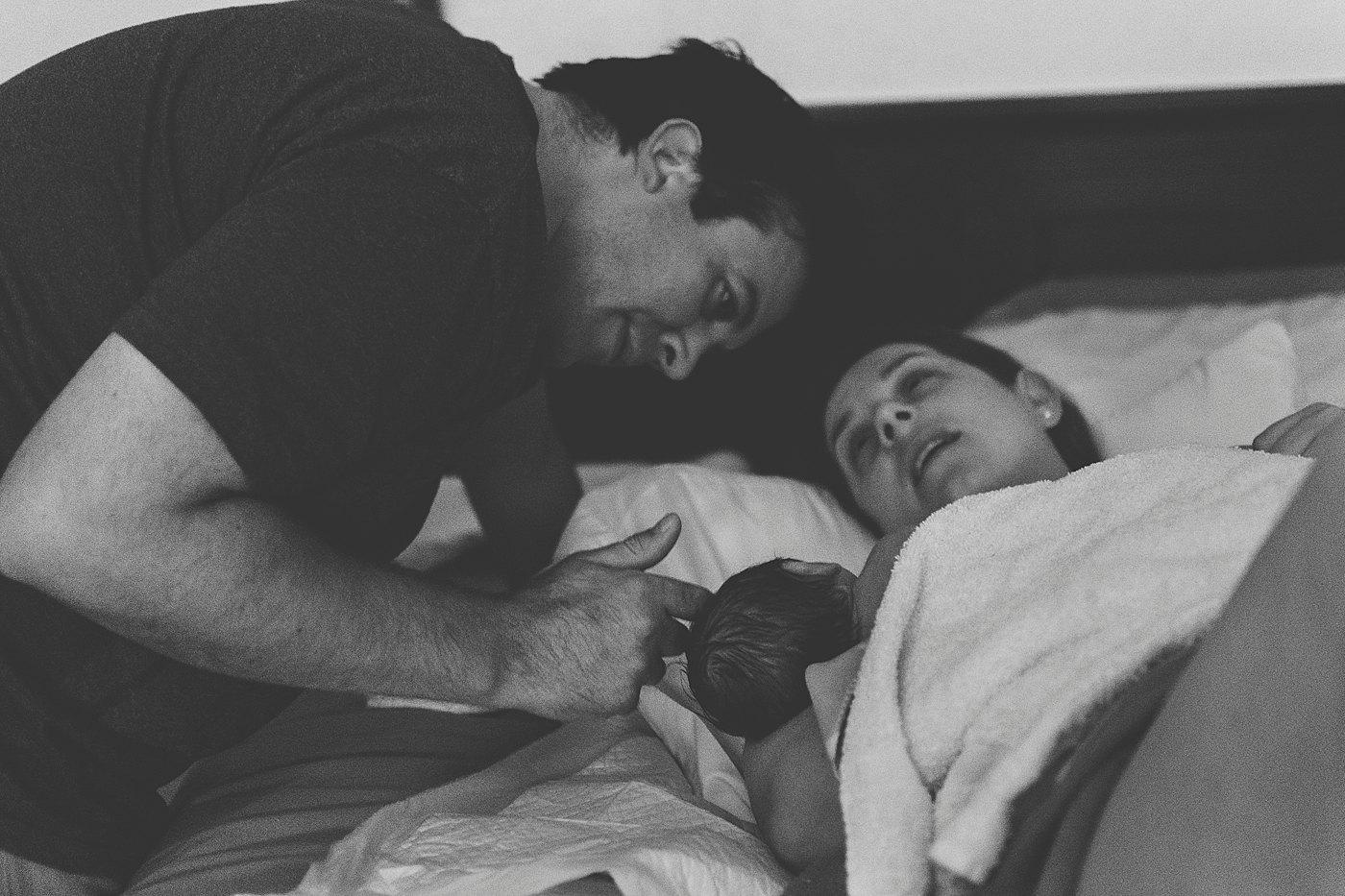 dad stroking newborn baby head as mom nurses after birth captured grace by erin yucaipa birth photographer