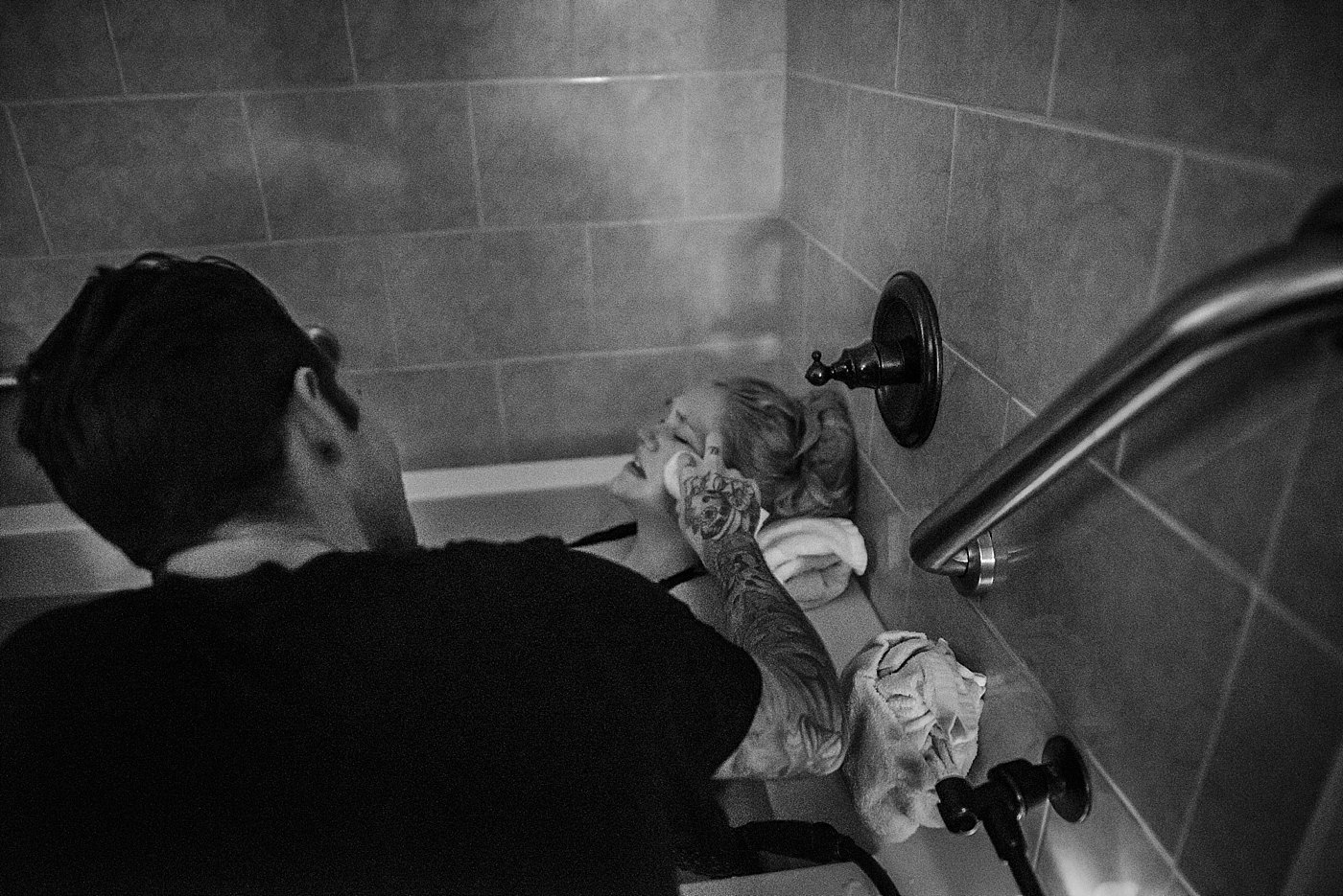 husband comforts wife during labor and birth redlands birth photographer