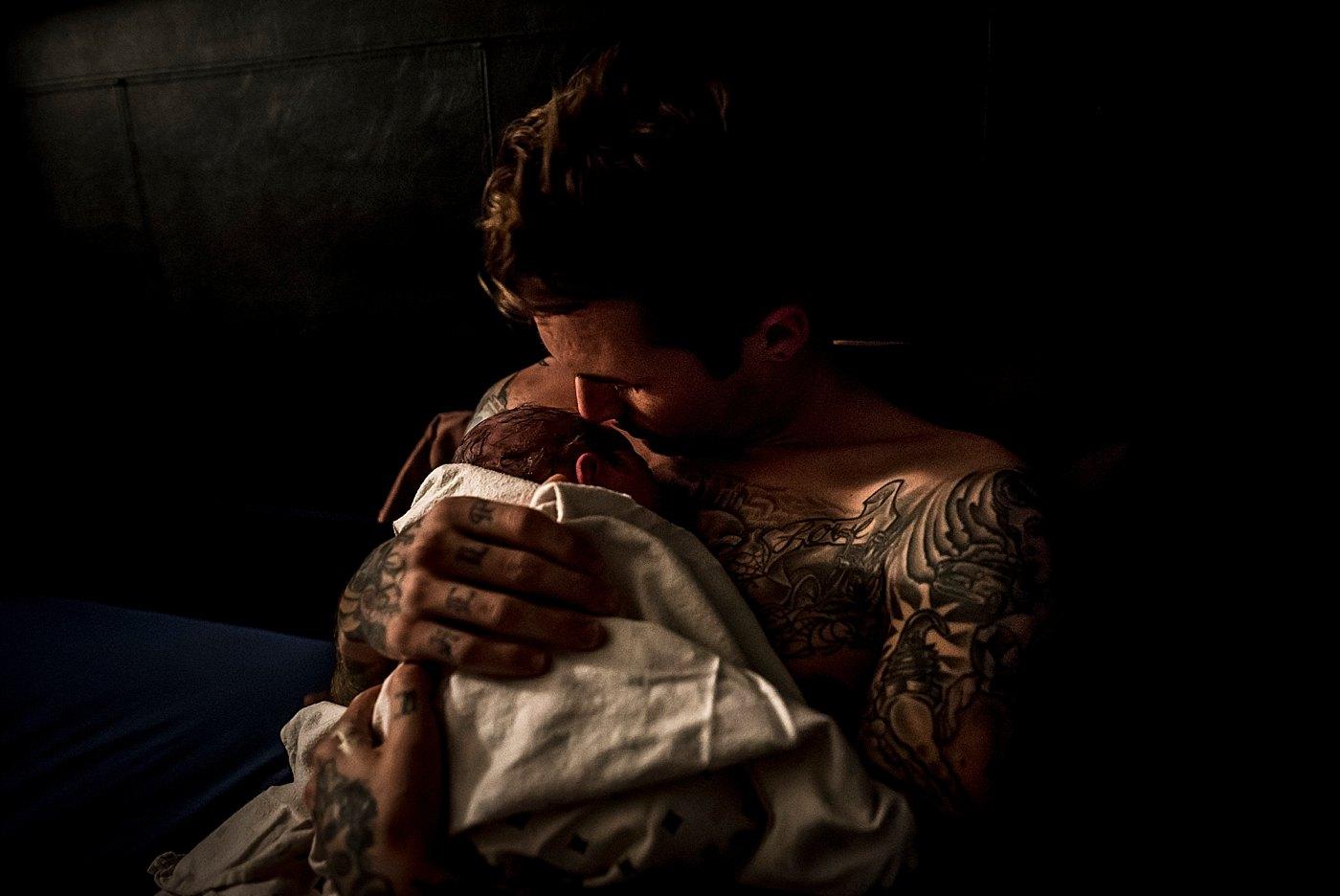 dad holding newborn son after birth redlands birth photographer