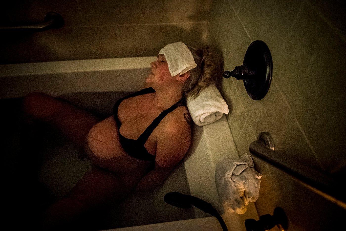 woman labors in birth tub at birth center redlands birth photographer