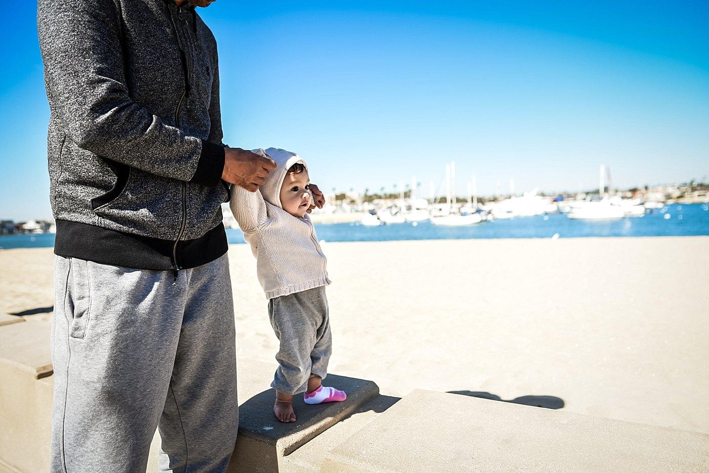 dad walking toddler daughter on beach