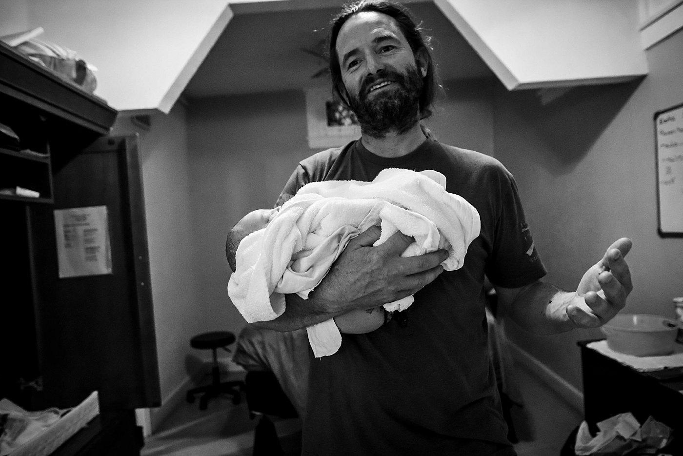 dad holds newborn son Yucaipa birth photographer