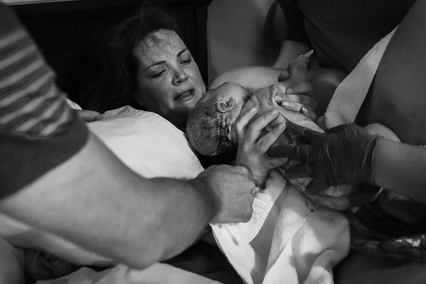 mom reaches for newborn baby Yucaipa birth photographer