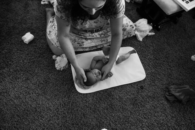 mom changing newborn diaper on floor redlands family photography