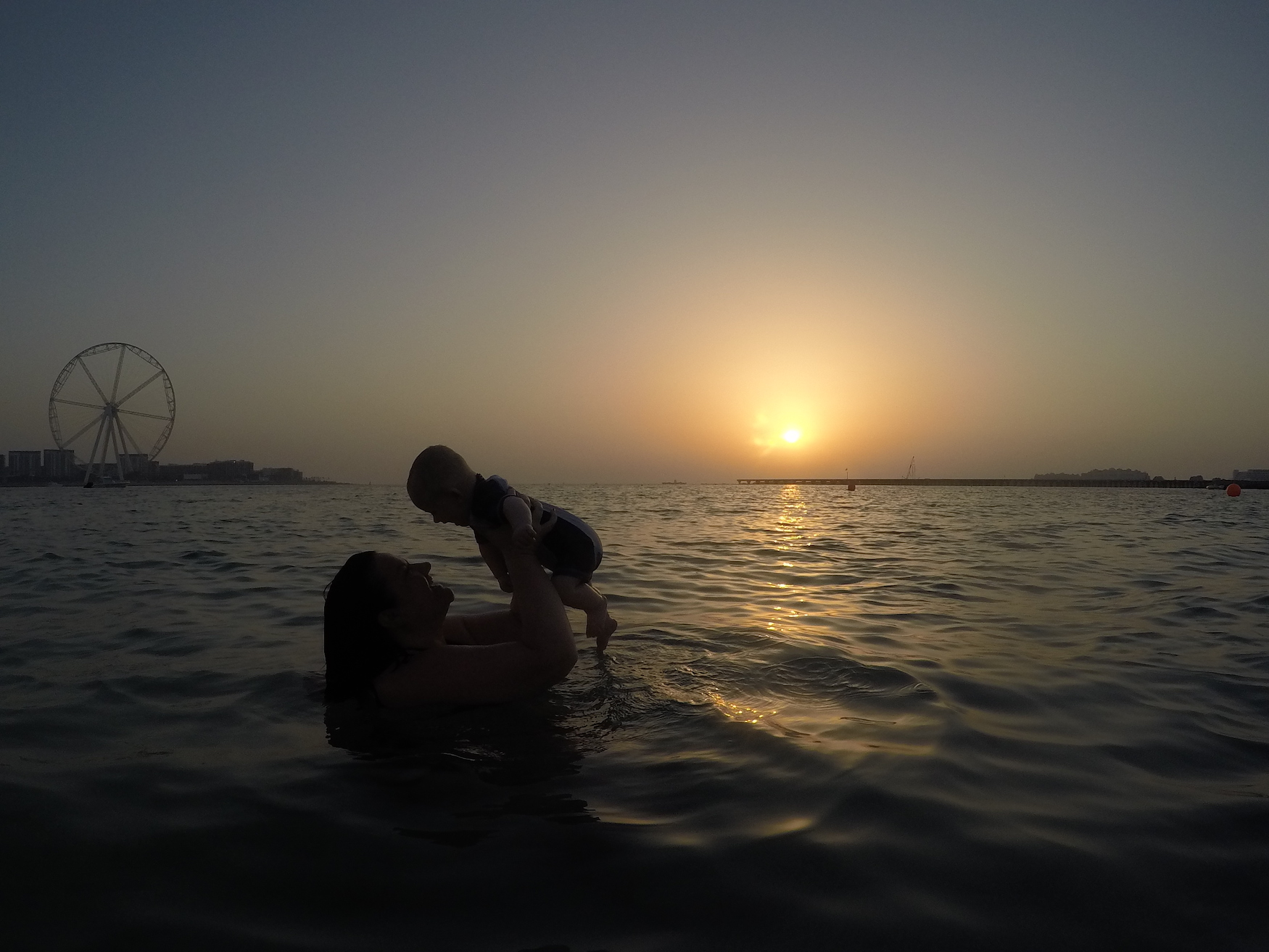 Mum holding up child in sea with sunset