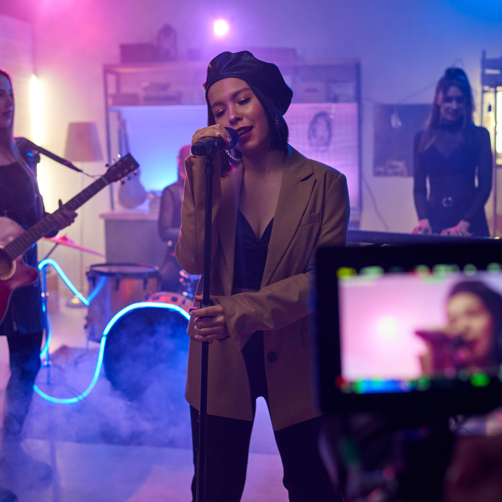 Singer singing in microphone while her group playing on musical instruments they shooting a music video