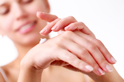 Smiling young woman applies cream on her hands. On a white background.