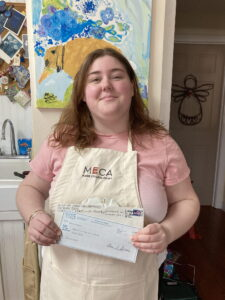 Abby is shown here with a just received $1,000 check.