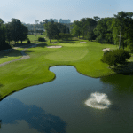 Hole 18 at Beachwood Golf Club with pond and water fountain