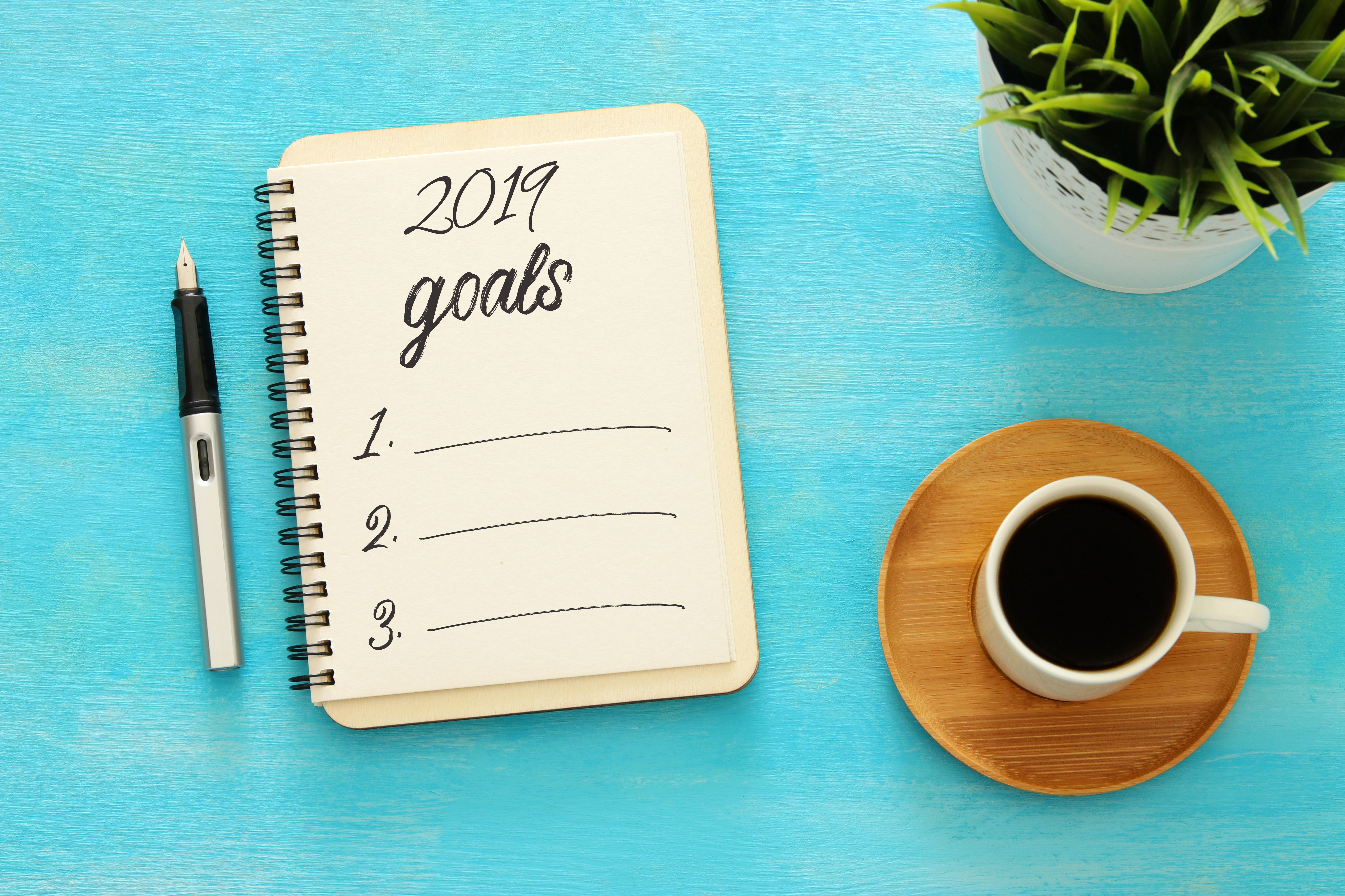 2019 goals list with notebook, cup of coffee over wooden desk