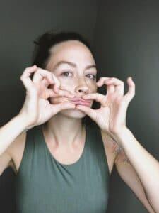 Esthetician performing facial massage on self