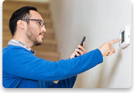 A man in a blue sweater uses his phone to adjust his thermostat.