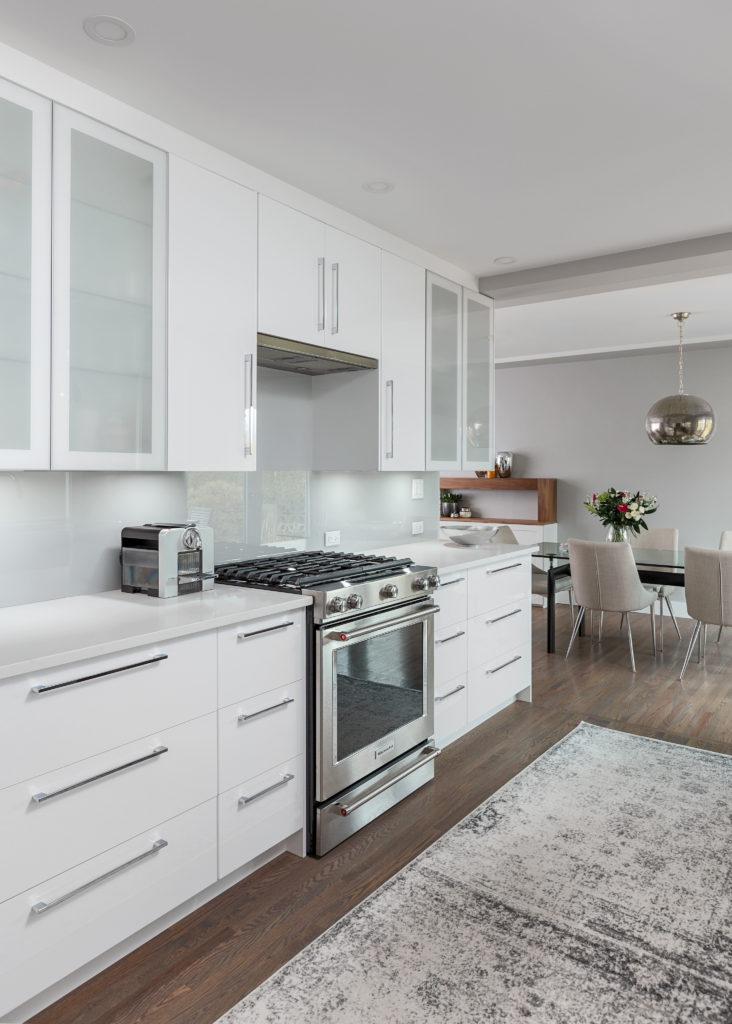 white gloss kitchen, gas stove, glass backsplash, nespresso, retractable range hood, ceasarstone