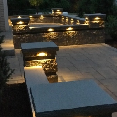 after two tiered patio with seating walls, custom gas fire pit and lighting