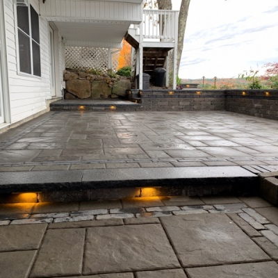 after 3 tiered patio with seating walls and lighting