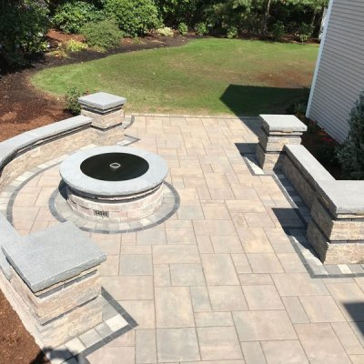 2 tiered patio with seating walls, custom fire pit, and lighting