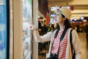 Finding the right vending machine location can make all the difference. A traveling woman with binoculars around her neck points at the glass of a vending machine at the airport.