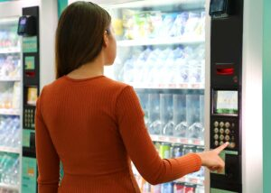 Location, selection, and cleanliness are the most common vending machine complaints. A woman in a burnt sienna blouse chooses a beverage from a vending machine.