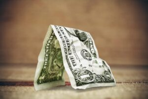 Crumpling or dirty dollars are reasons why vending machines reject bills. A crumpled dollar bill in an A shape..