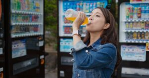 Vending machine placement is vital to improved success, specially when you can have multiple machines at one locale. A woman drinks orange soda she got from a vending machine.