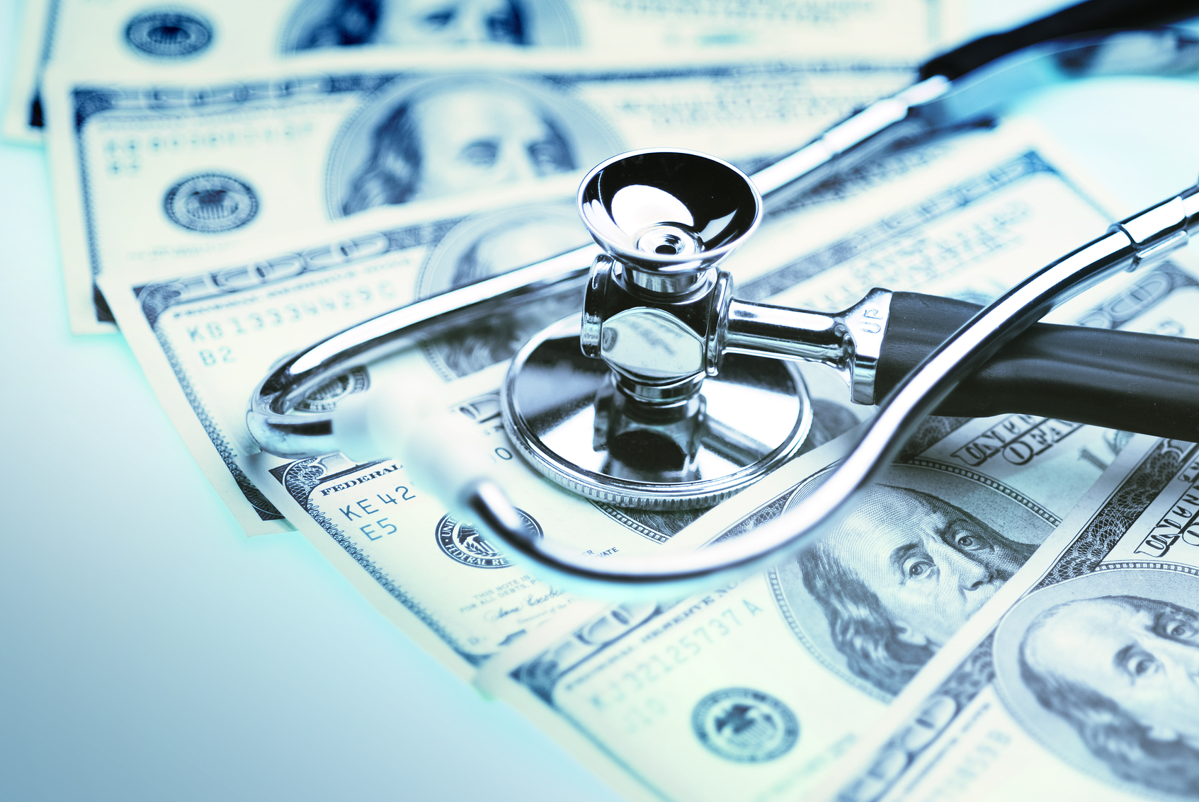 Money and stethoscope to illustrate the cost of health care