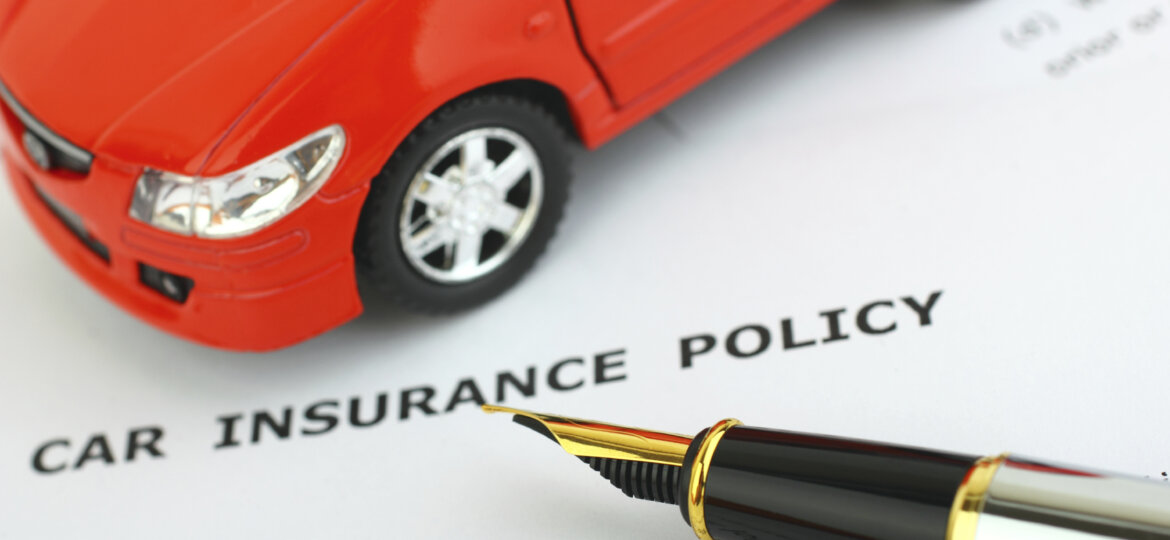 Toy car on top of auto insurance policy