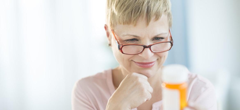 Woman with glasses holding prescription bottle