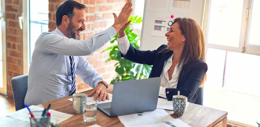 Man and woman giving high five at desk