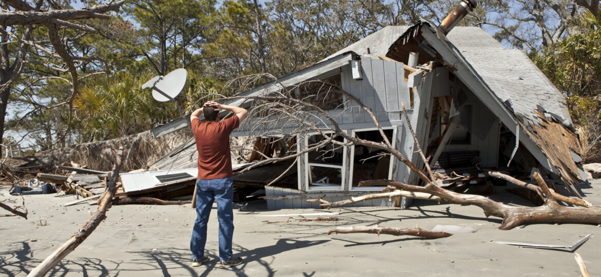 Man in front of damaged home