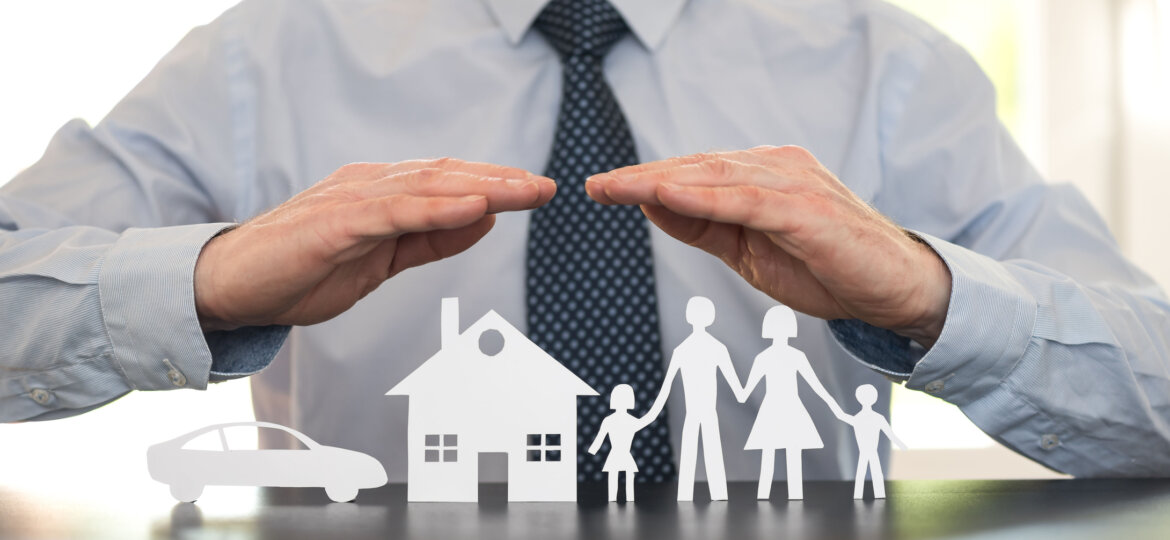 Man with hands over cutout family