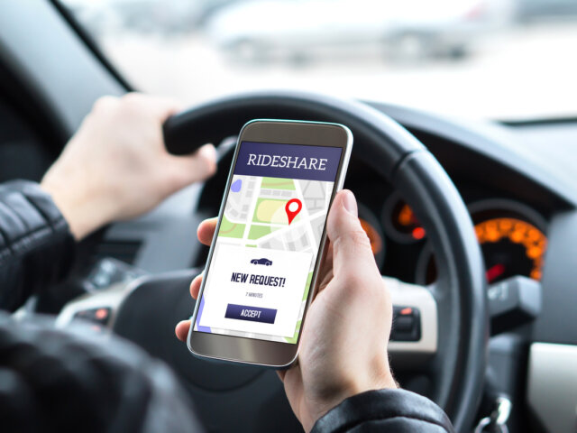 Ride share driver in car using the rideshare app in mobile phone. New taxi ride request from customer in smartphone application.