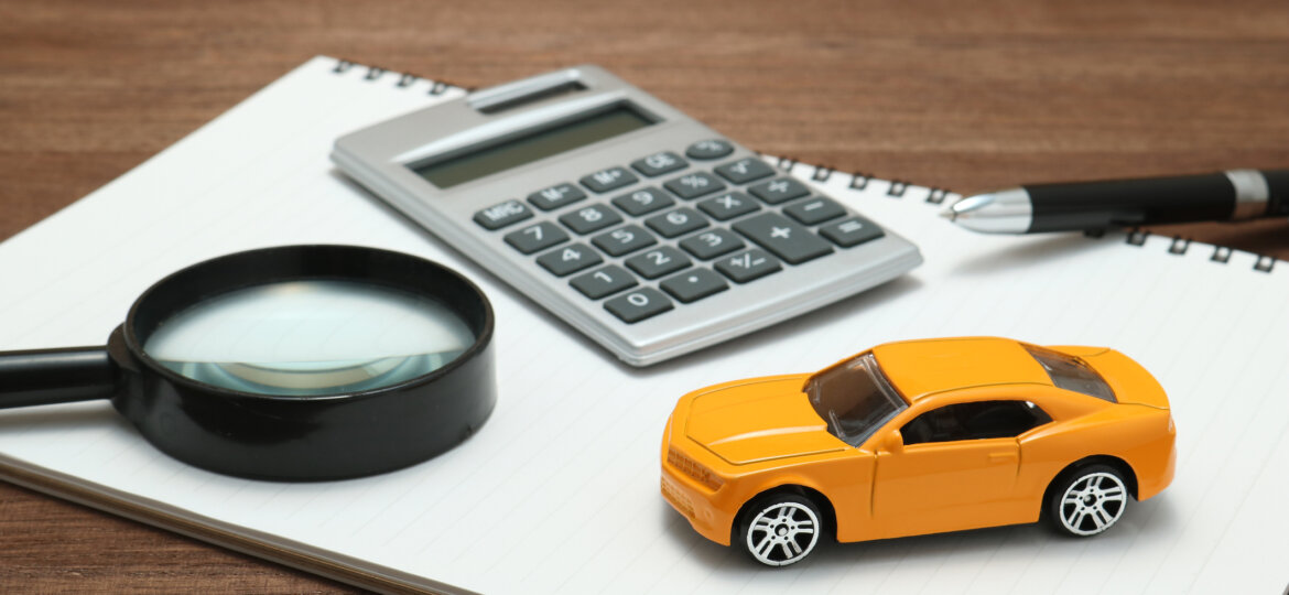 Toy car, magnifying glass, calculator, pen and notebook