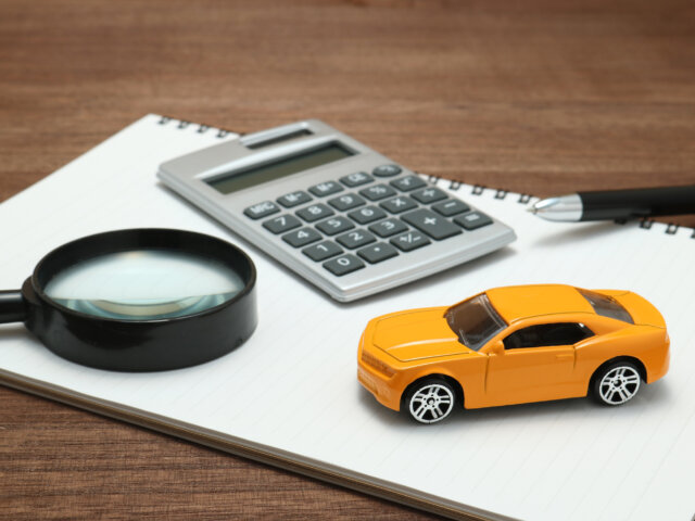 Toy car, magnifying glass, calculator, pen and notebook.