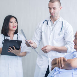 Two doctors talking with patient
