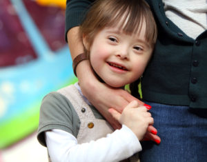 A young girl with Down syndrome is having fun with her mom.