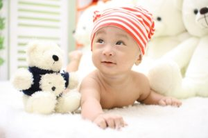 A young baby boy wearing a knit cap is pictured with stuffed animals.
