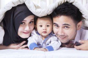 A muslim family peeks under a blanket