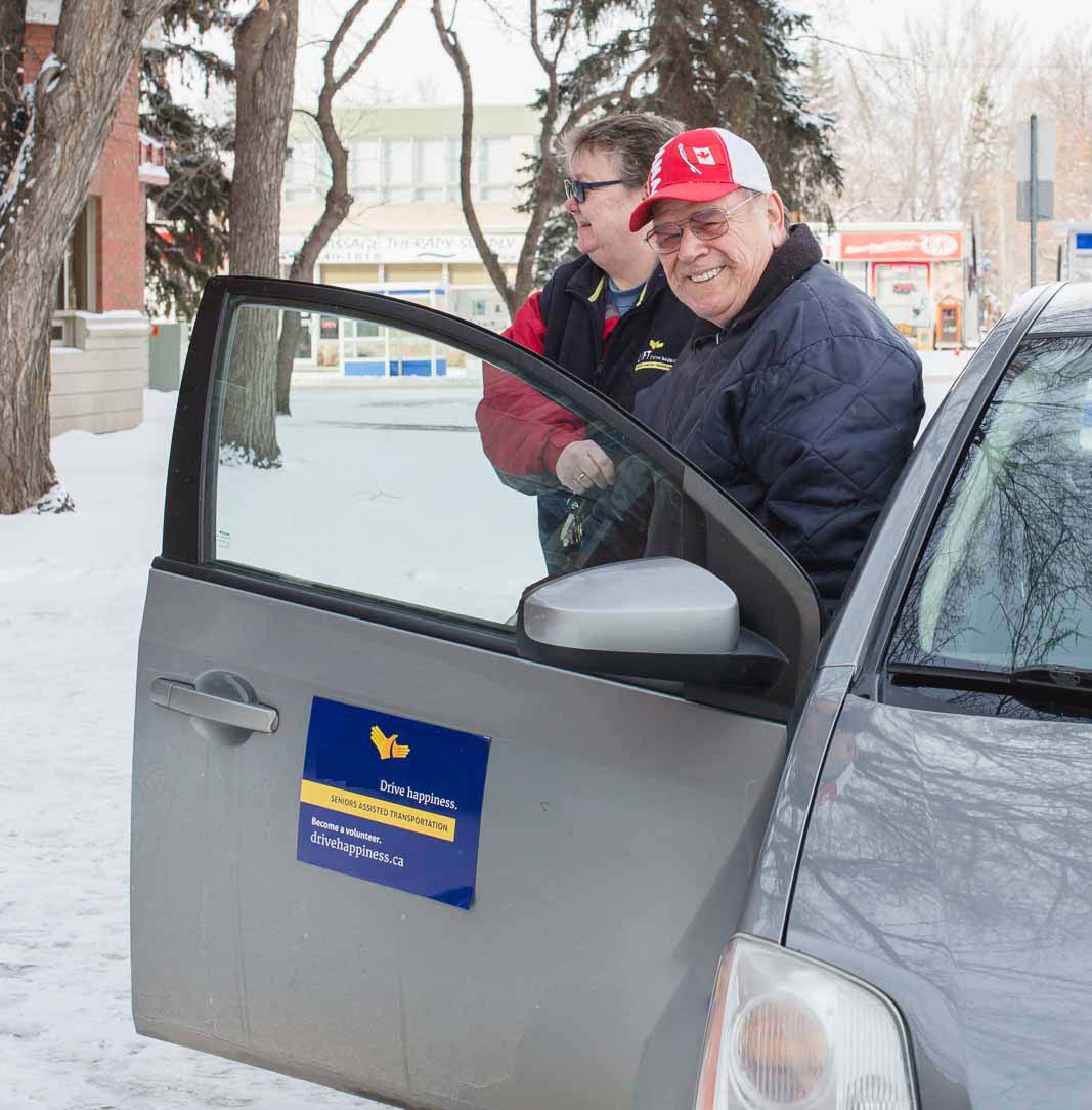 Volunteer driver helps a senior out of a car