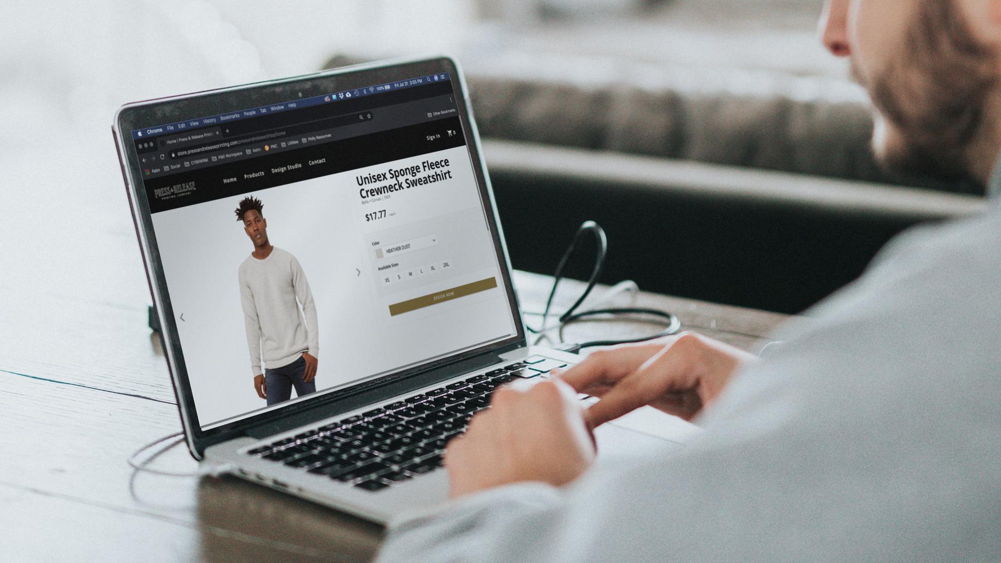 man researching crewnecks on internet