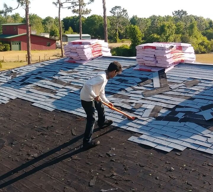 Roofer removing roof shingles for a roof replacement in Kissimmee, Florida