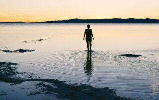 Person standing with ankles in the Great Salt Lake at golden hour. This Inland Sea is a rich source of minerals to help prevent trace mineral deficiency. Photo credit tory-morrison-661217-unsplash