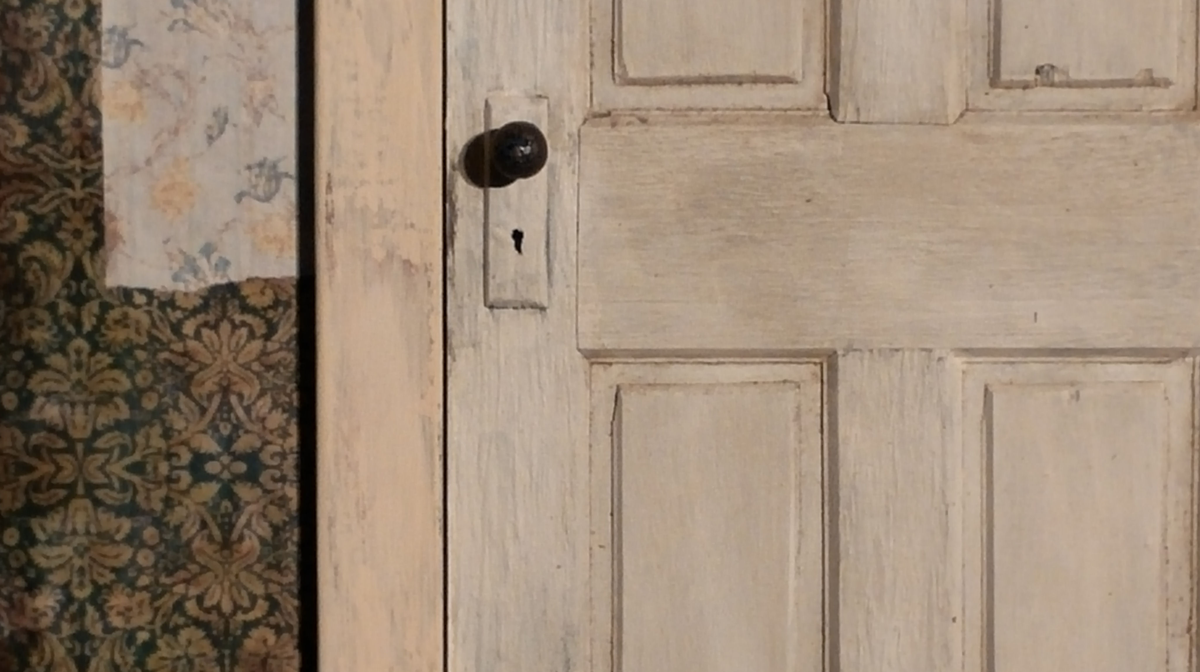 white-door-with-tattered-wallpaper-close-up
